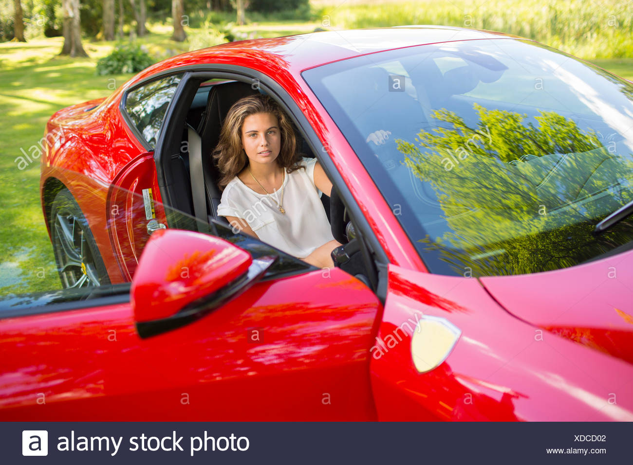 Sweden, Ostergotland, Mjolby, Teenage girl (14-15) sitting in red car - Stock Image