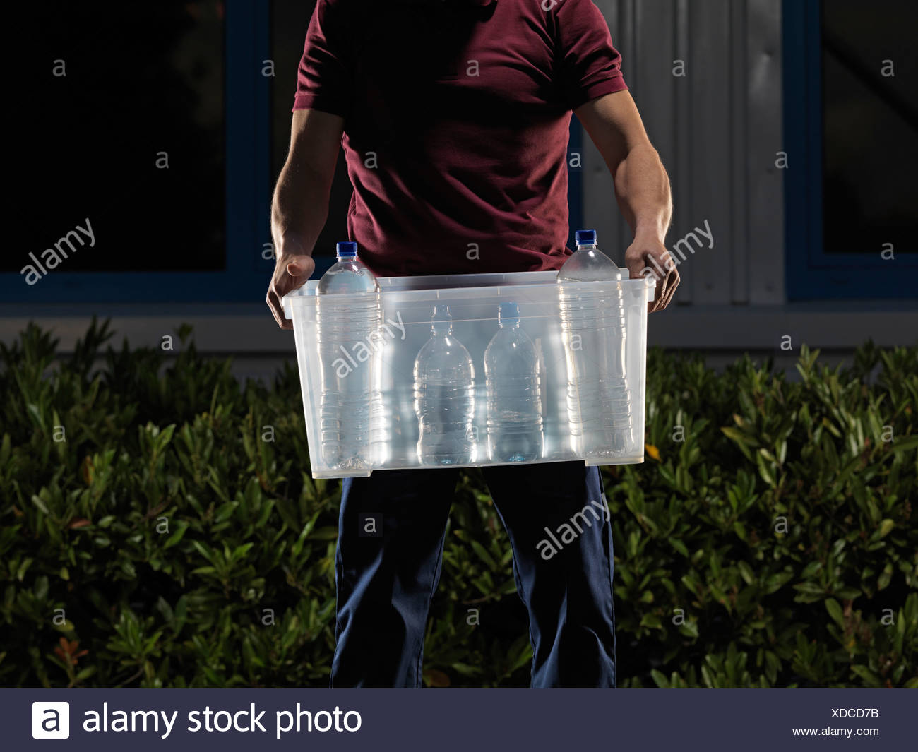 man carrying box of water at night - Stock Image