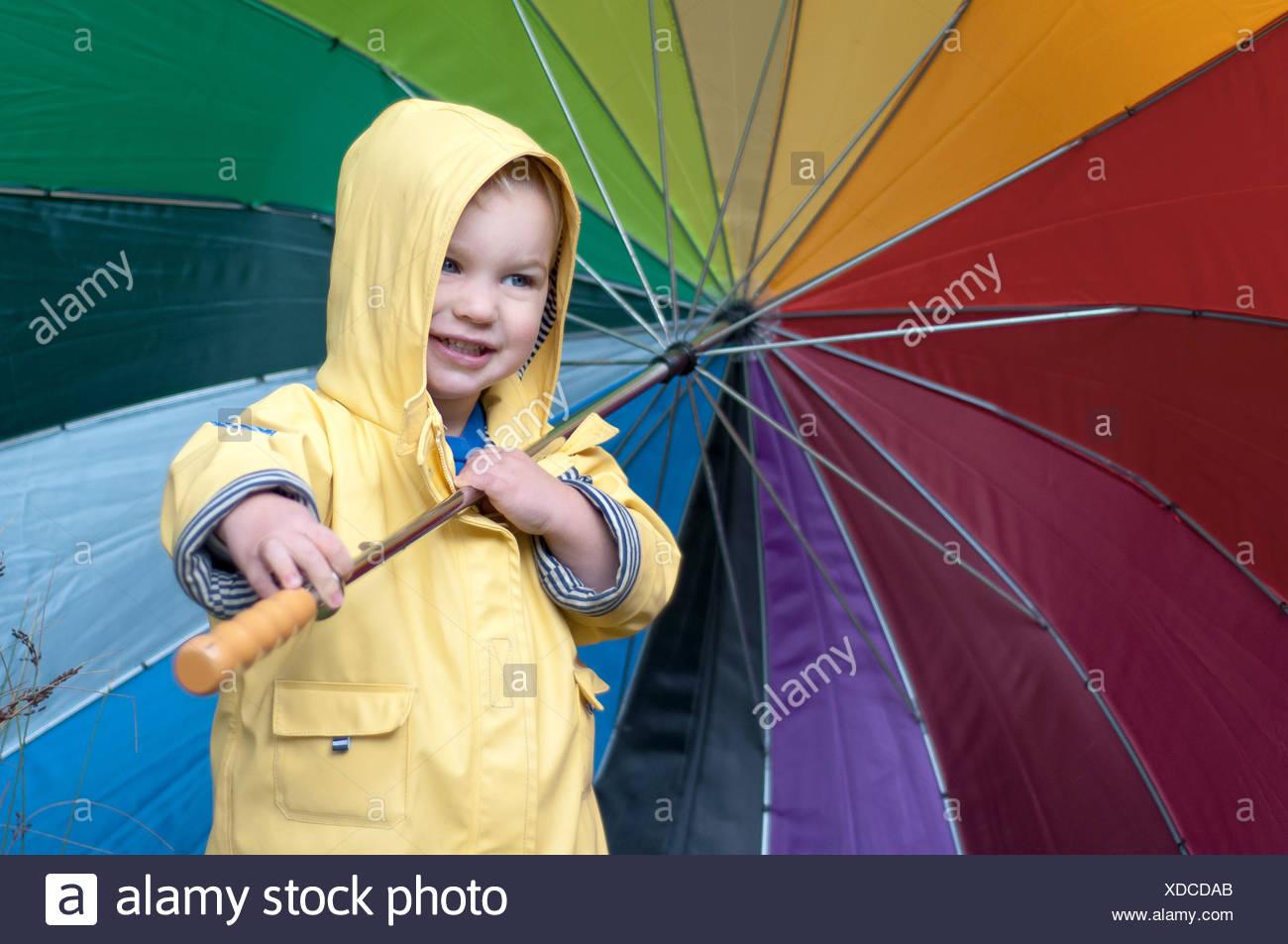 Boy in a rain coat holding multi-colored umbrella - Stock Image