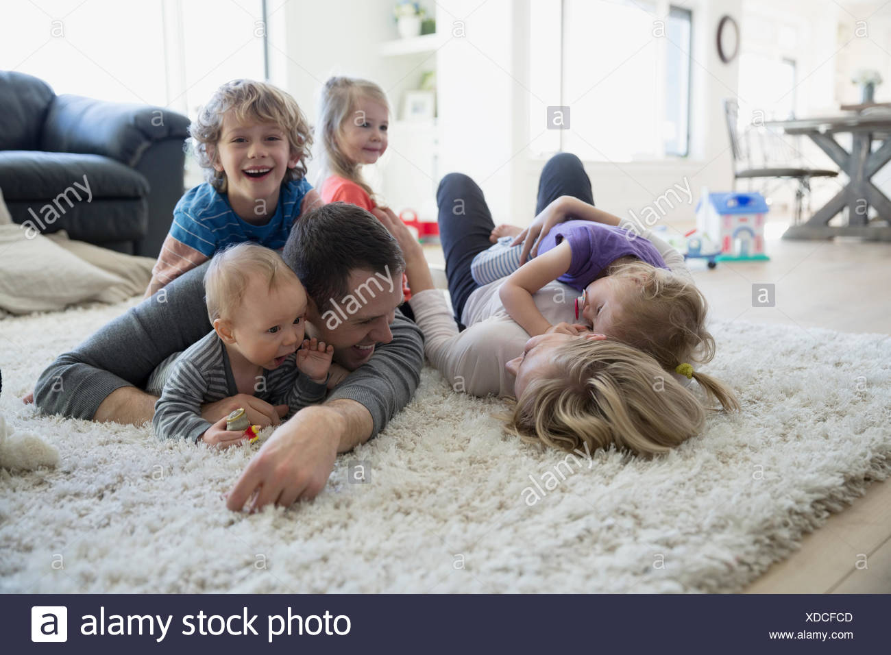 Family laying and relaxing on shag rug - Stock Image