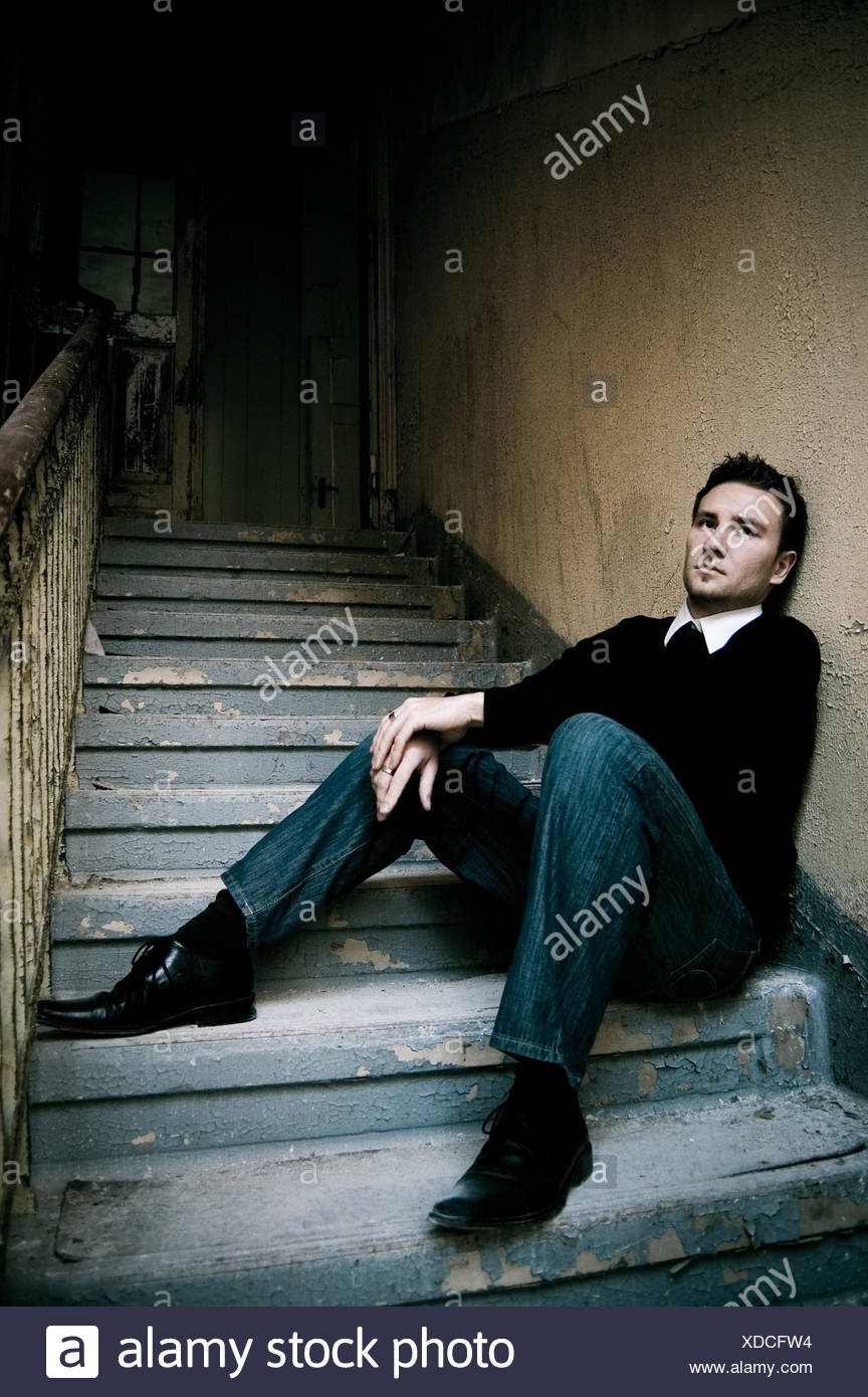 young man,pensive,lonely,stairway - Stock Image