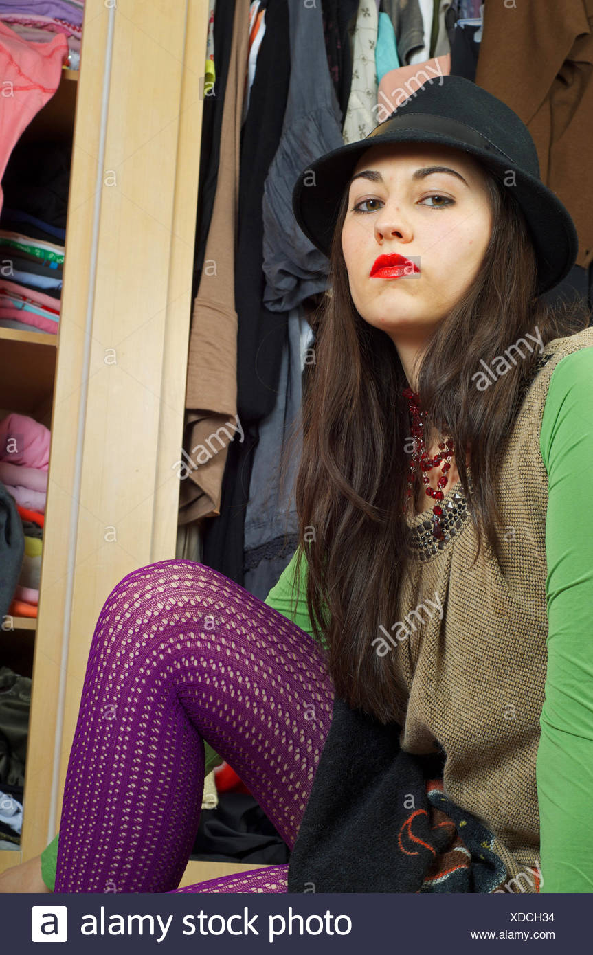 young woman sitting in front of a garderobe - Stock Image