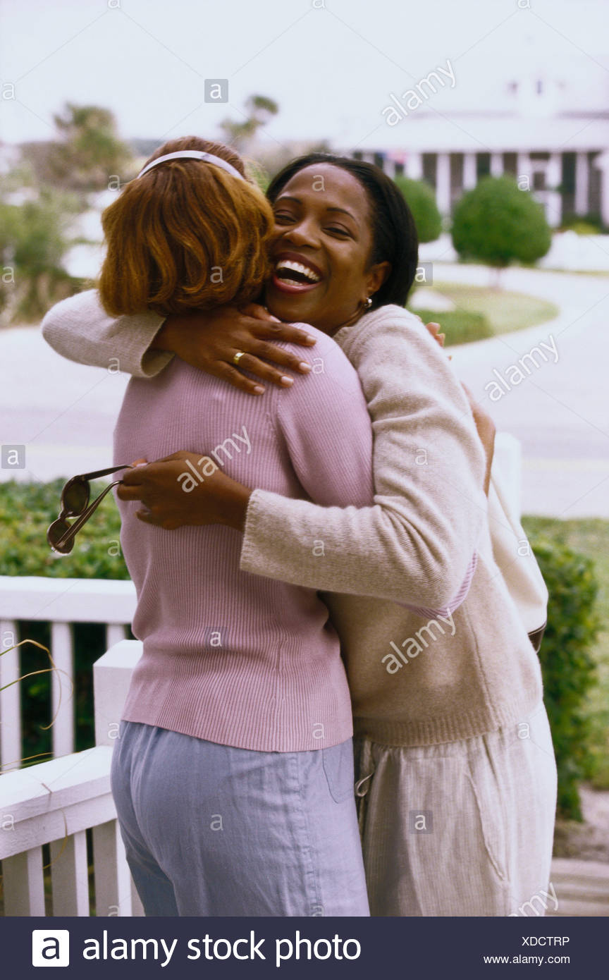 Rear view of a mother hugging her daughter on the porch - Stock Image