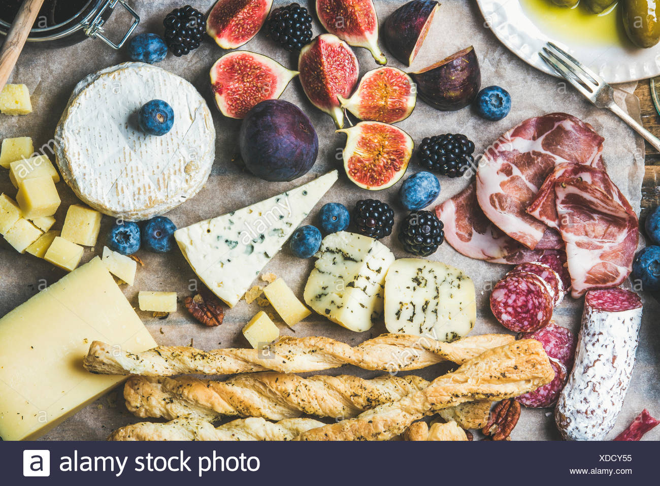 Close-up of wine snack set with meat variety, bread, green olives, figs, nuts and berries on wax paper, top view, horizontal com - Stock Image