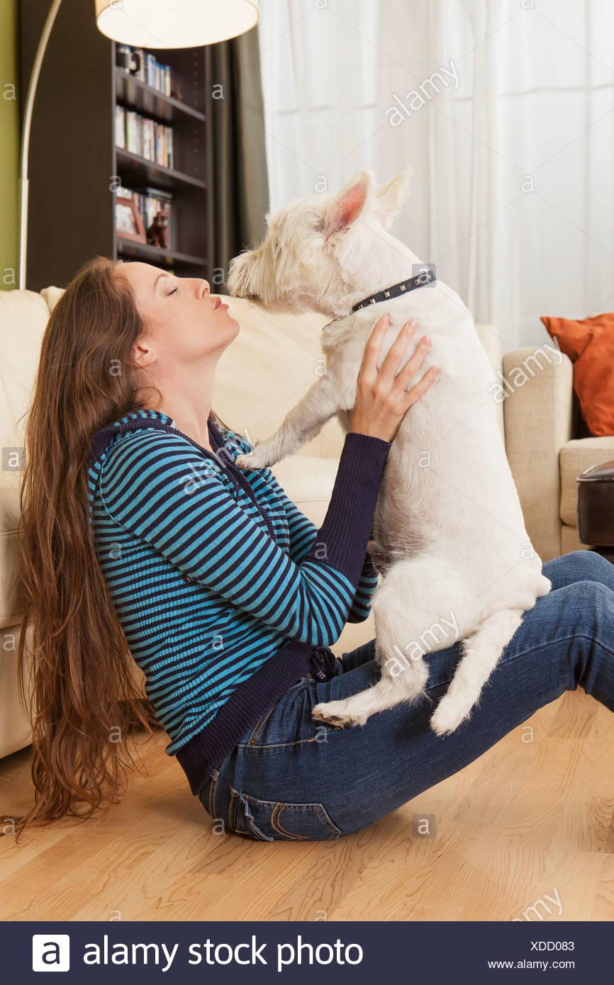 Woman kissing her dog - Stock Image