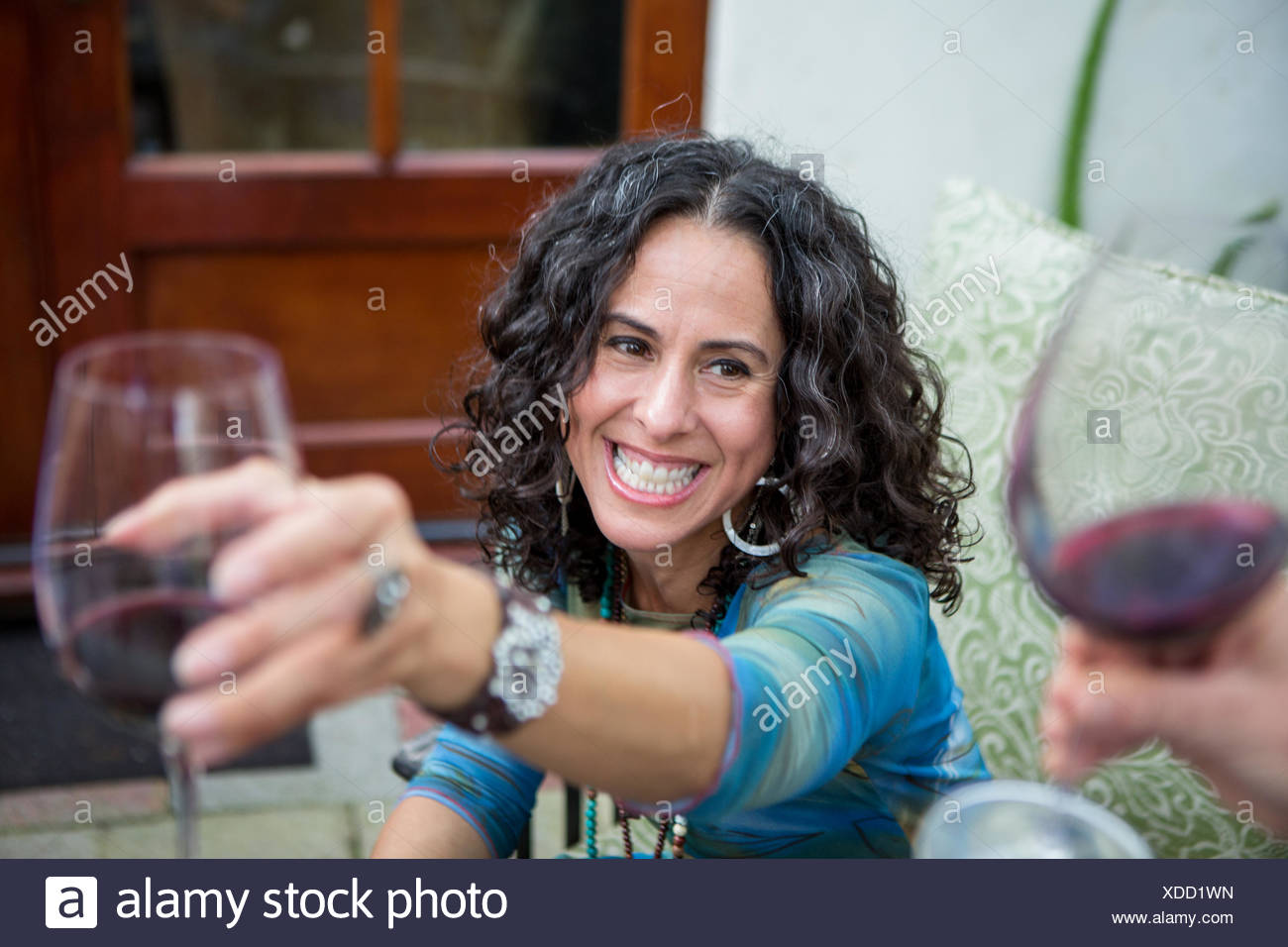 Over shoulder view of mature women making red wine toast at garden party - Stock Image