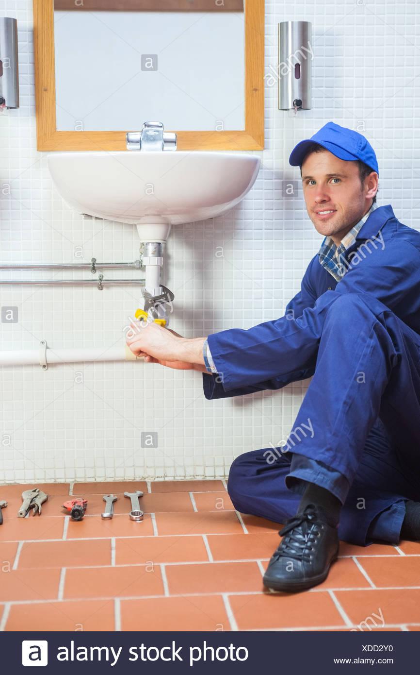 Smiling plumber repairing sink - Stock Image