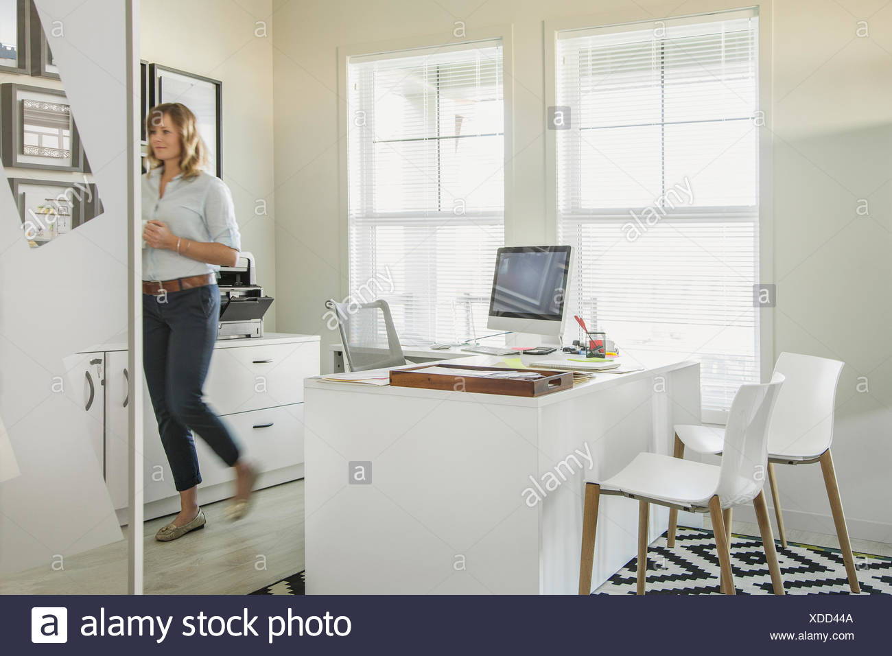 Woman walking in home office - Stock Image