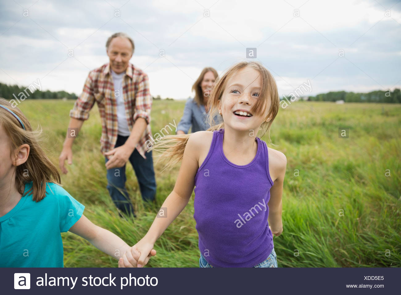 Grandparents chasing granddaughters in field - Stock Image