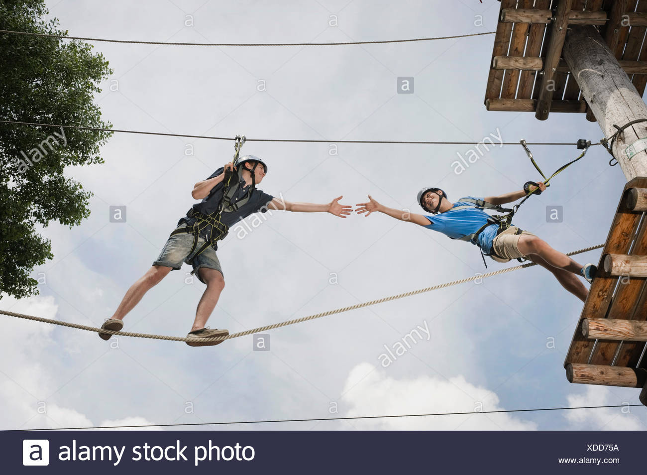 teenager in a climbing crag helping another - Stock Image