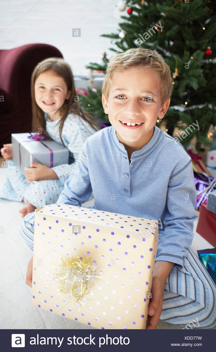 Brother and sister holding gifts sitting by christmas tree, portrait - Stock Image