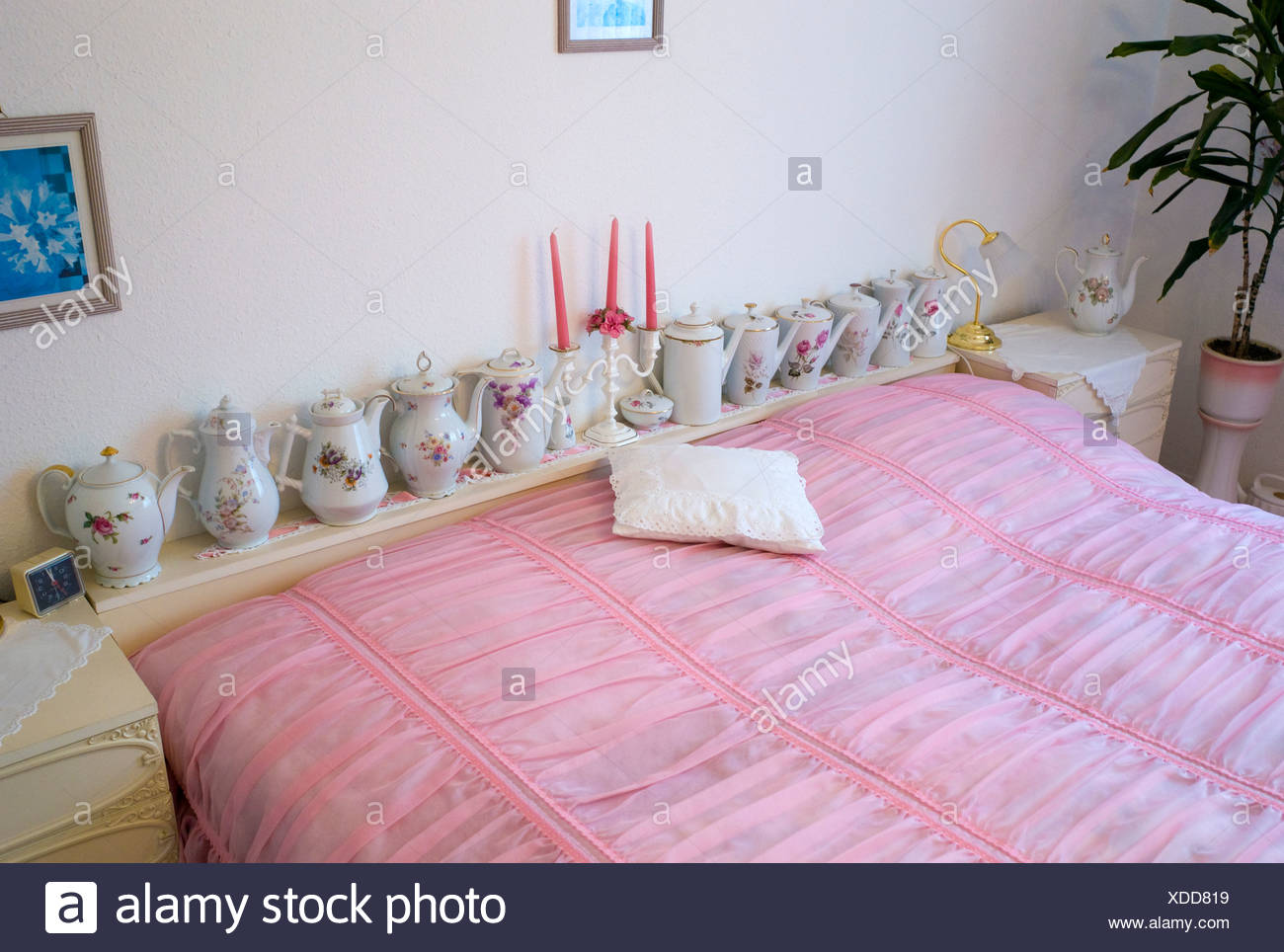 Old fashioned bedroom with pink bedspread and teapots, Germany, Europe - Stock Image
