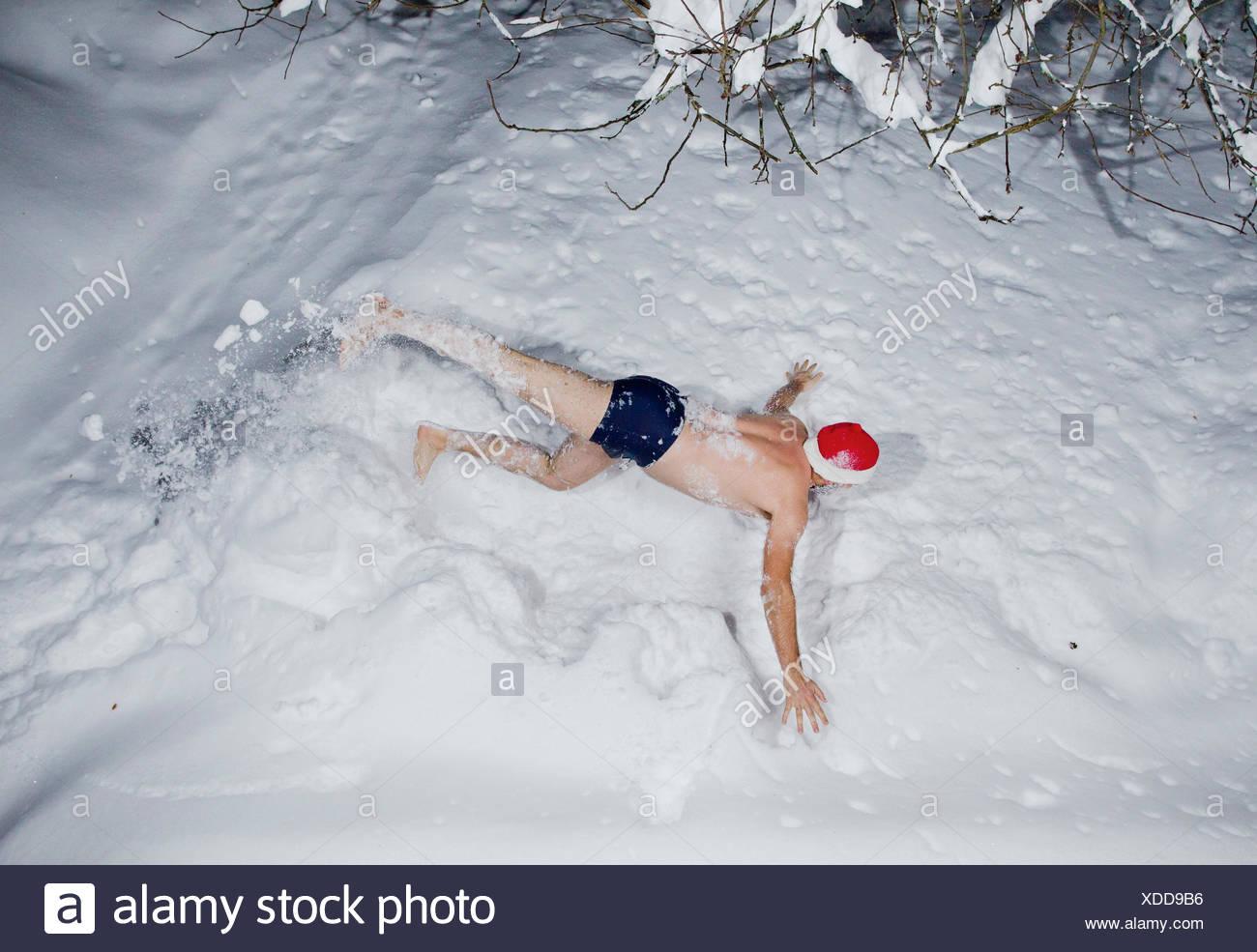 Finland, Heinola, Man lying down on snow undressed - Stock Image
