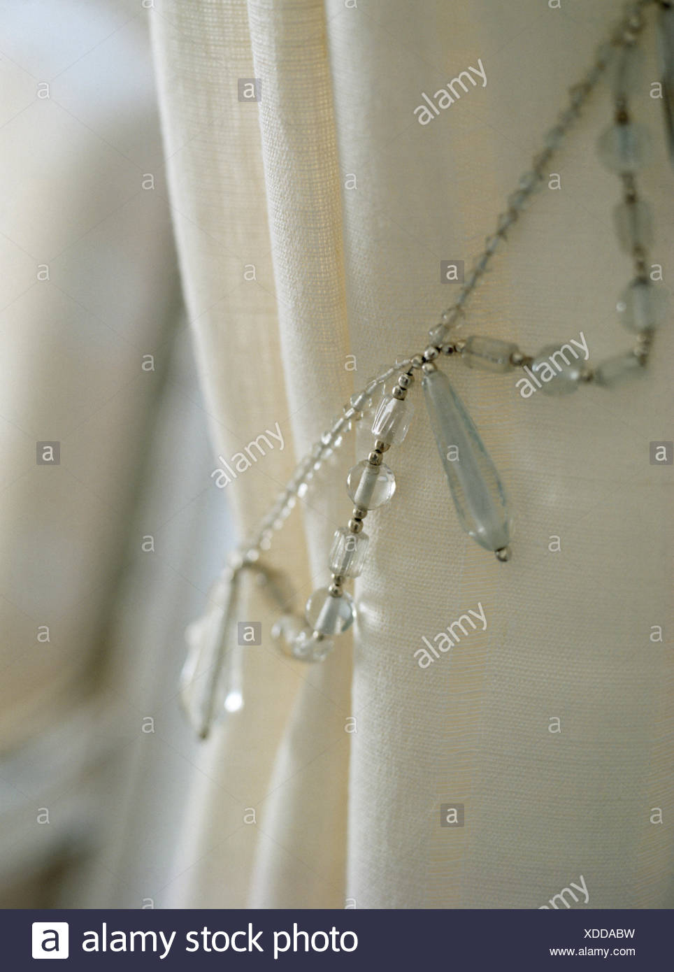 Close-up of white curtain with beaded tie back - Stock Image