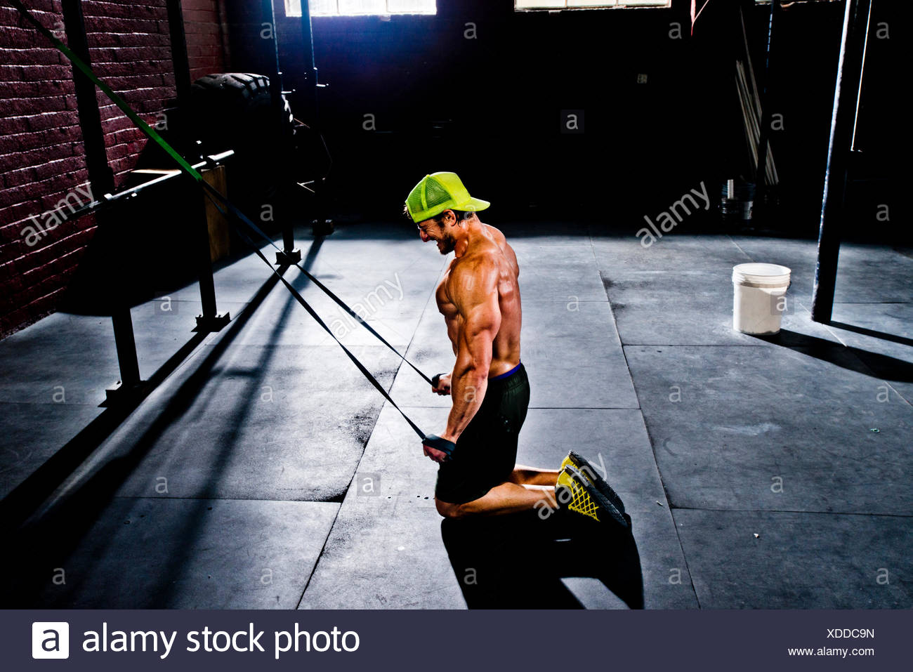 A crossfit athlete working out with resistance bands. - Stock Image