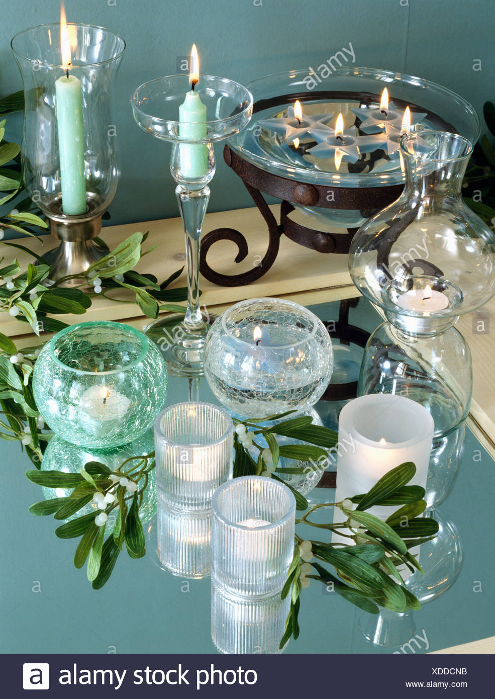 Close-up of glass candle holders and bowl with lighted turquoise and white candles - Stock Image