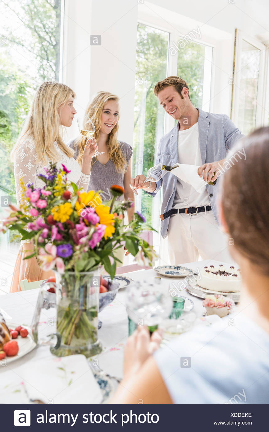 Young man pouring champagne for family at birthday party - Stock Image