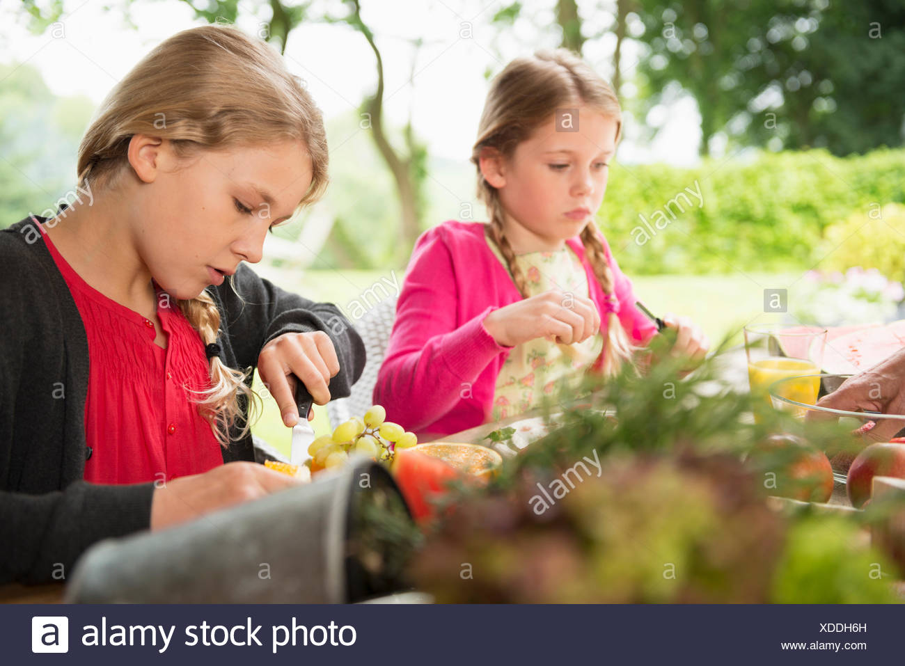 Two sisters at patio table slicing fresh fruit - Stock Image