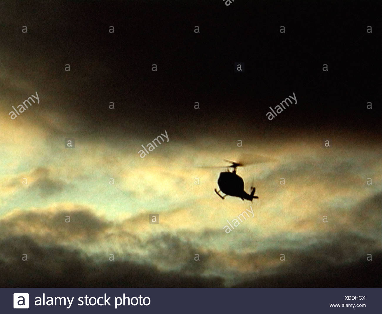 Helicopter in cloudy sky - Stock Image