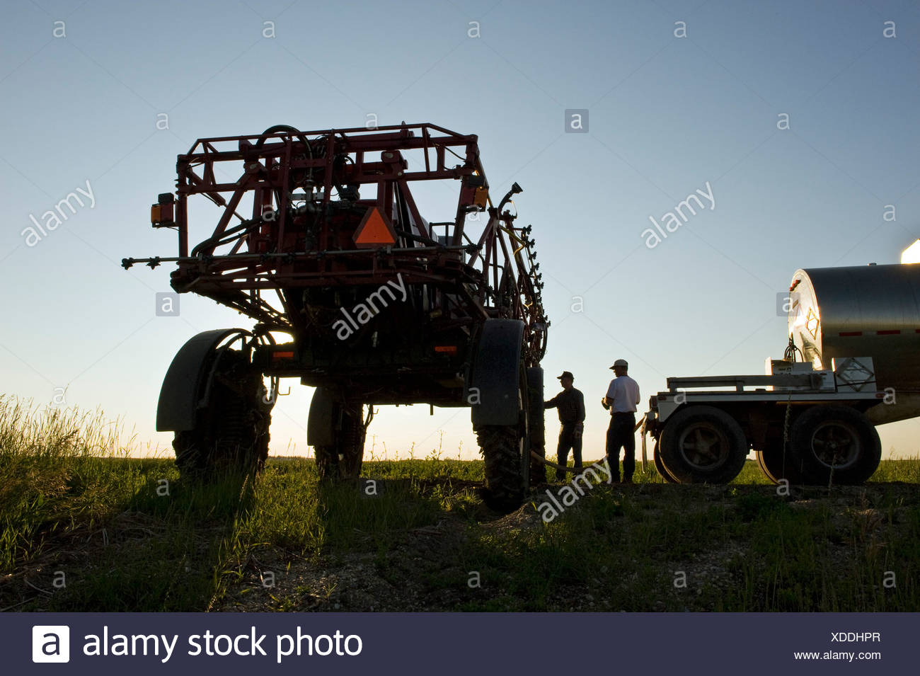 Two farmers load a high clearance sprayer with chemical