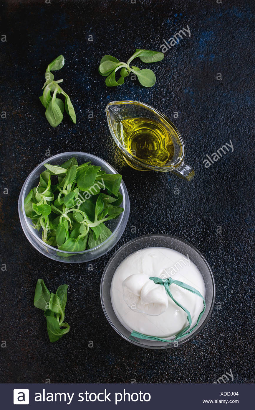 Whole tied Italian cheese burrata in brine served with fresh corn salad and olive oil in glass bowls over dark textural backgrou - Stock Image