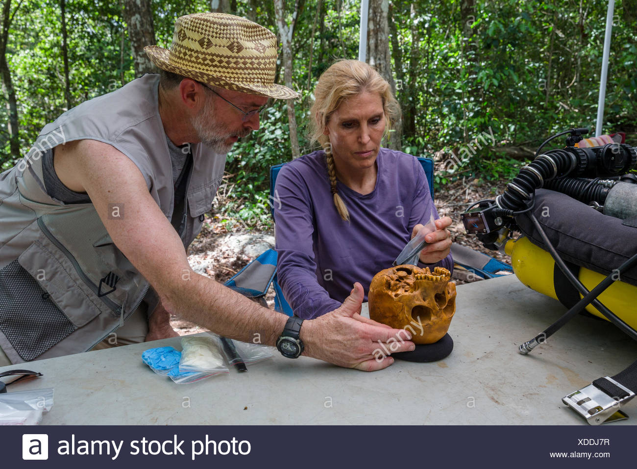 Team member and archeologist examine a replica of the skull of 'Naia,' a girl, who died between 12,000 and 13,000 years ago. - Stock Image