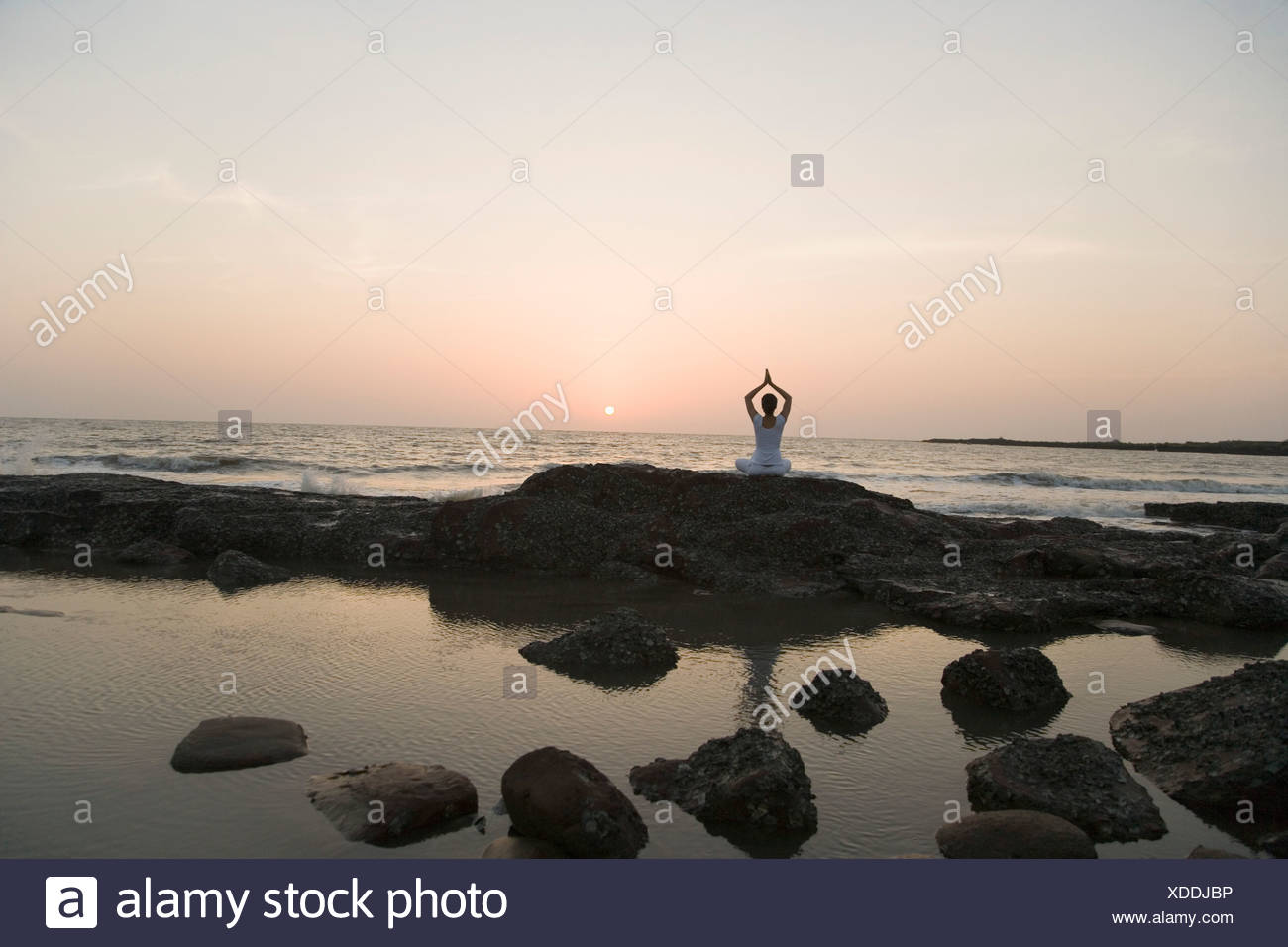 Rear view of a woman practicing yoga on the coast - Stock Image