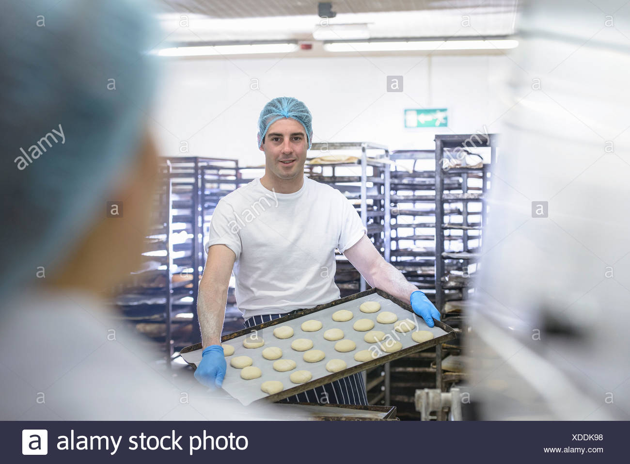 Baker holding tray of prepared dough ready for the oven - Stock Image
