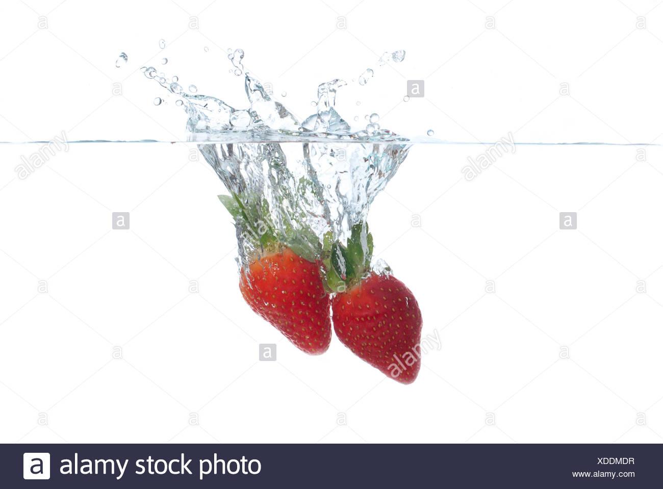 Strawberries splashing into water - Stock Image