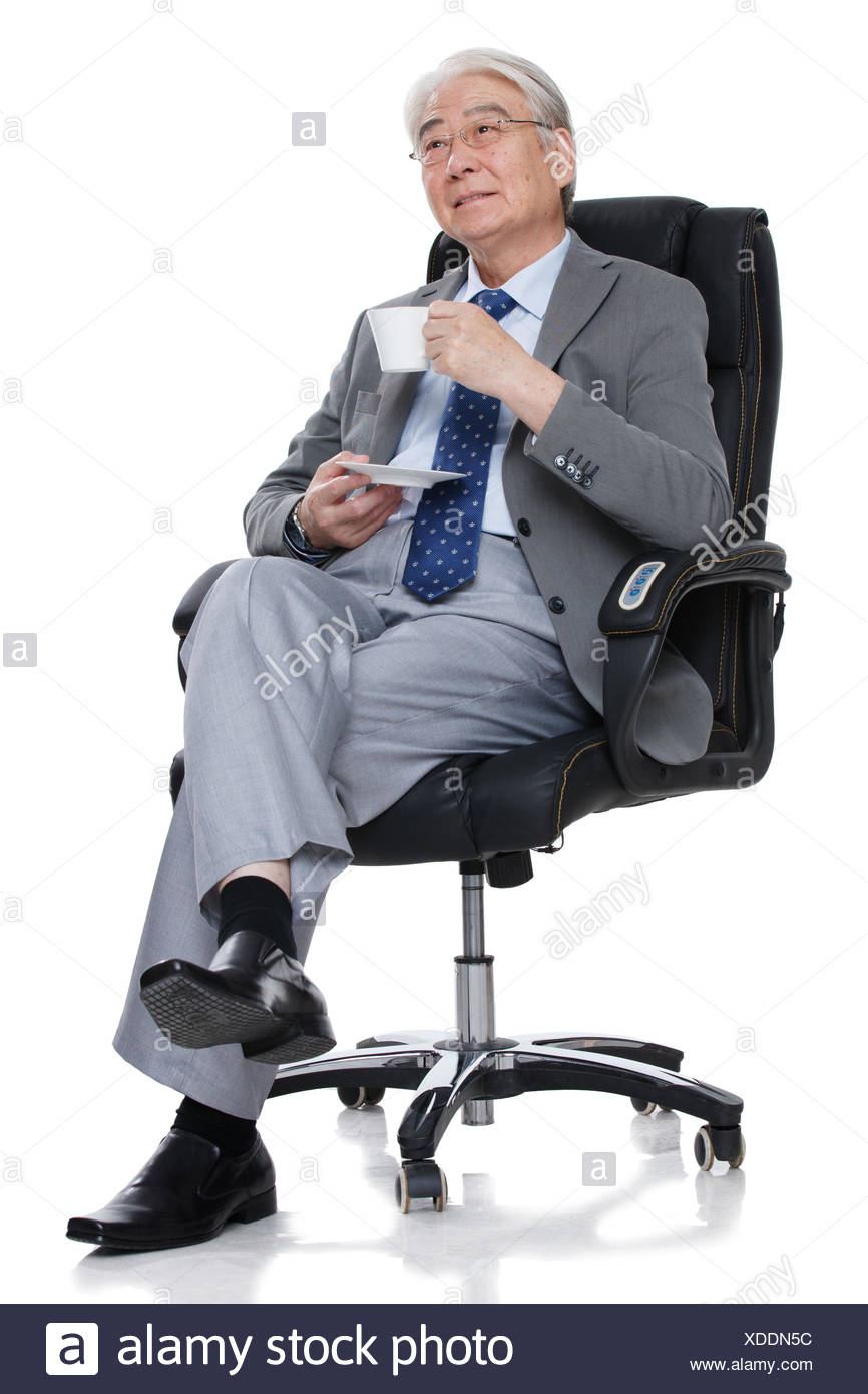 A sitting in the boss's chair to drink Coffee old man - Stock Image