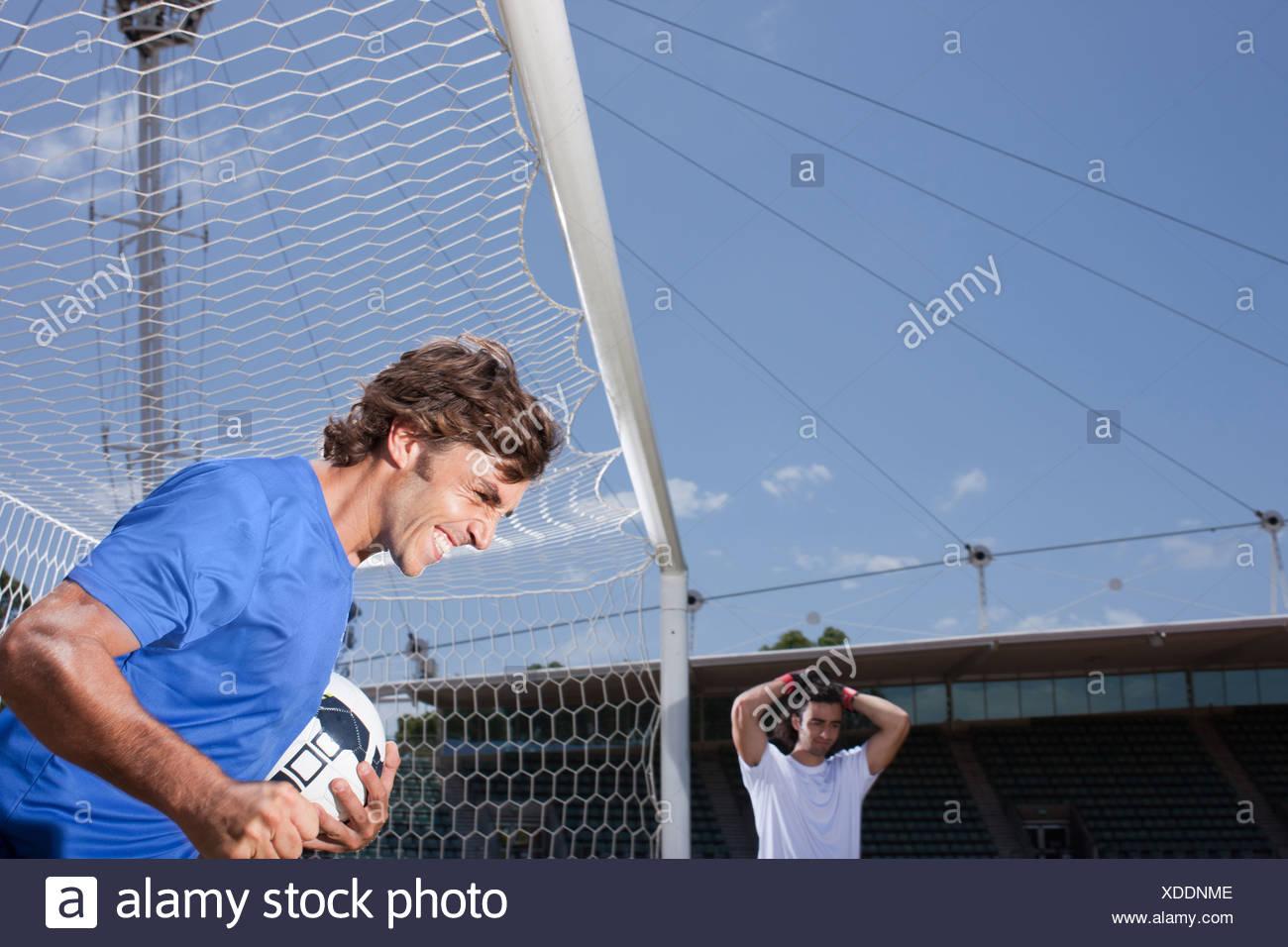 Soccer player scoring goal - Stock Image