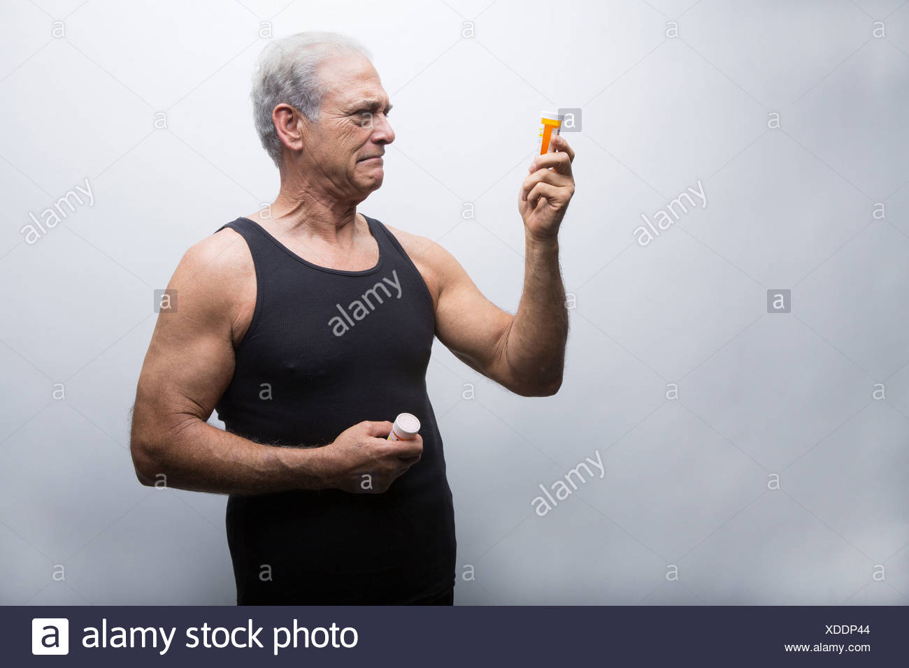 Senior man looking at pill bottles - Stock Image