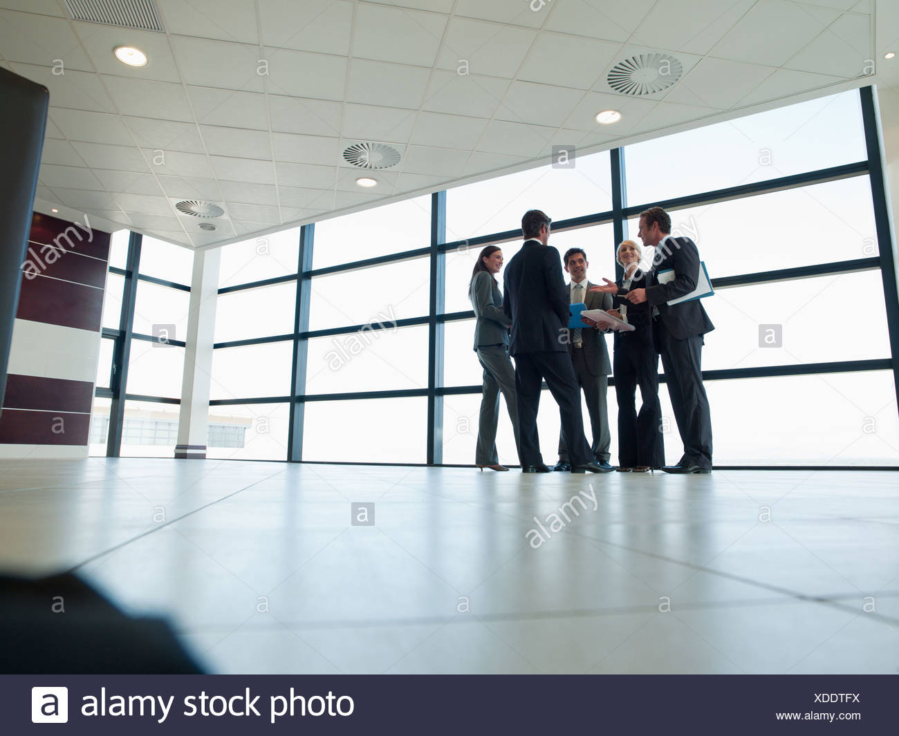 Business people talking in lobby - Stock Image