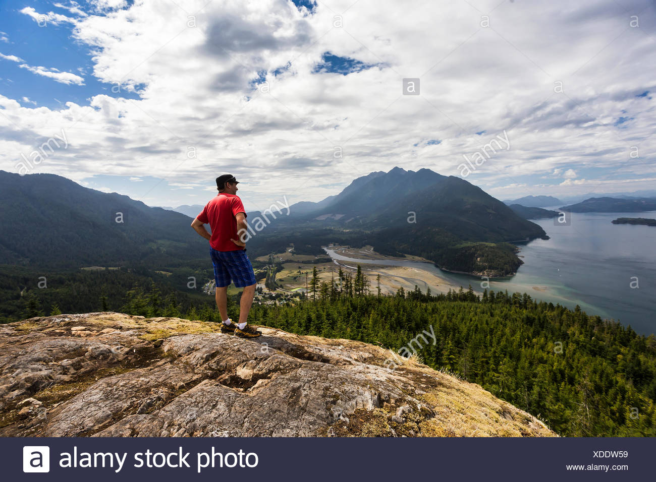 A hiker is rewarded with commanding views of Kelsey Bay, Johnstone strait and the Salmon River Estuary from a viewpoint high above the valley,  Sayward, Vancouver Island. - Stock Image