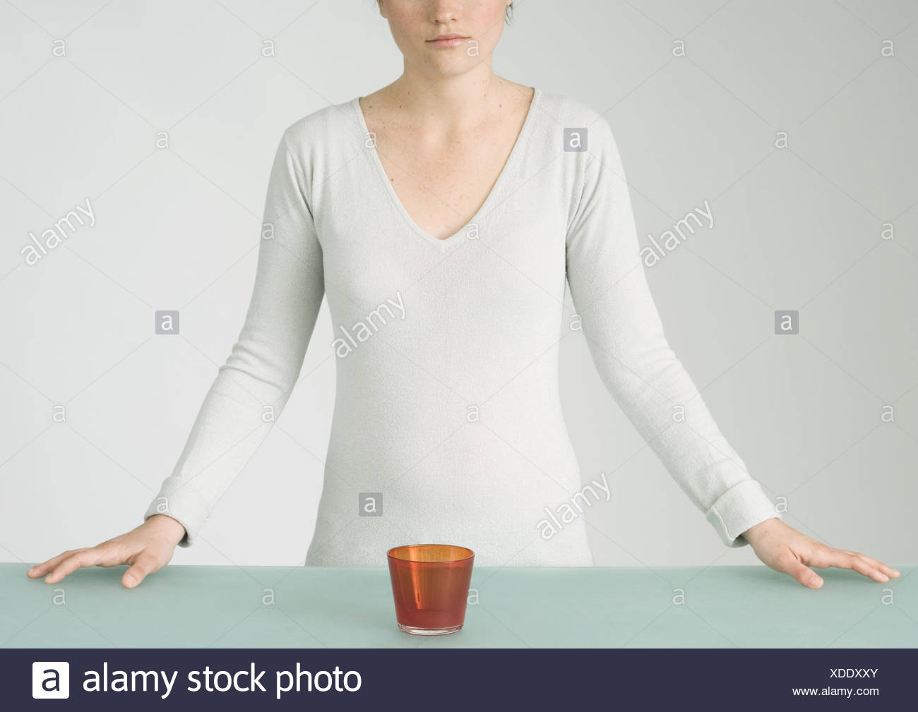 Young woman standing with glass in front of her on table, partial view - Stock Image