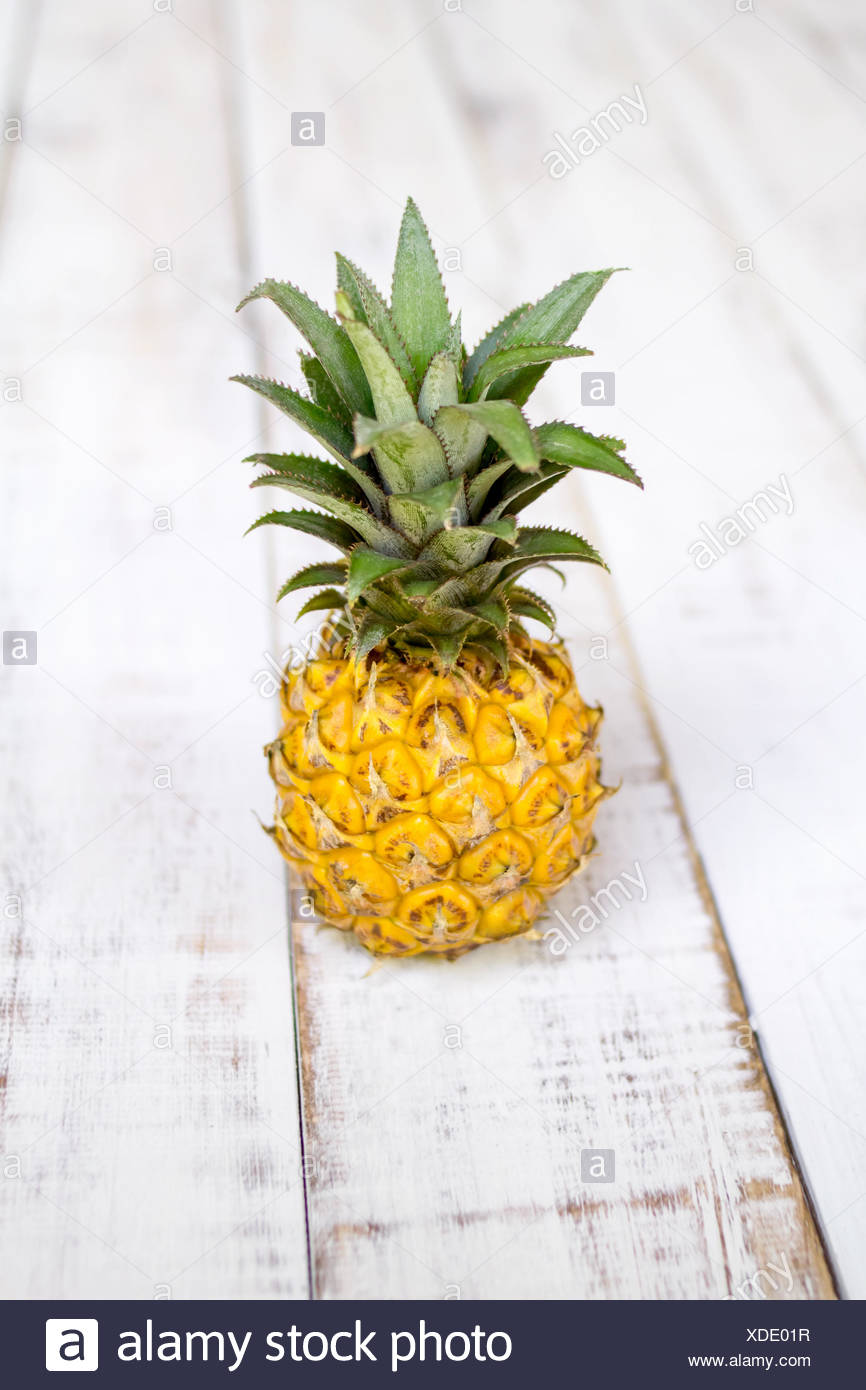 Close-up of a pineapple on a wooden table - Stock Image