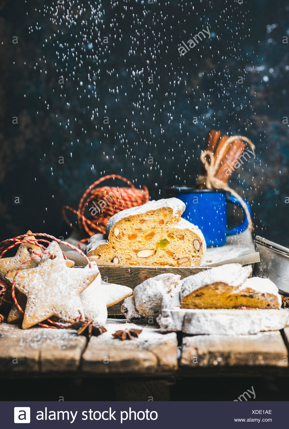 Piece of Traditional German Christmas cake Stollen with festive gingerbread star shaped cookies and falling sugar powder, selective focus, dark blue g - Stock Image