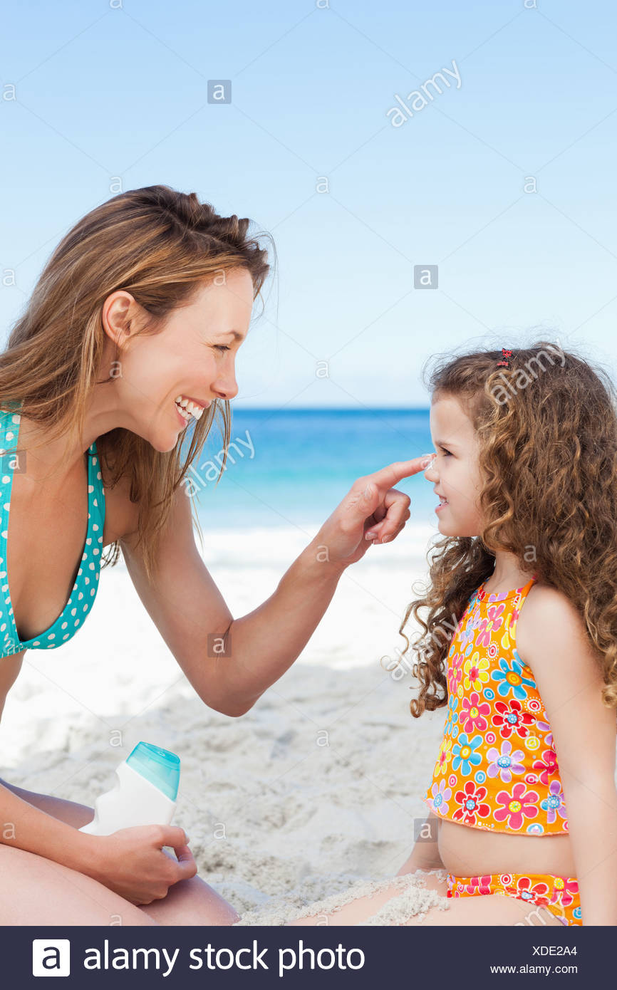Mother applying sunblock on her daughters nose on the beach - Stock Image