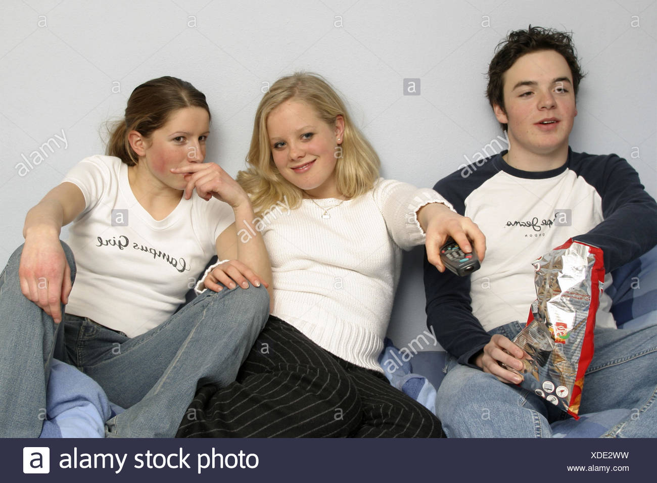 Teenagers, boy, girl, watch TV, zap, eat crisps, happy, only positive use 17 years, young persons, teenagers, three, friendship, friends, remote control, toggle, cycle selection, television evening, activity, entertainment, consumer electronics, fun, amus - Stock Image