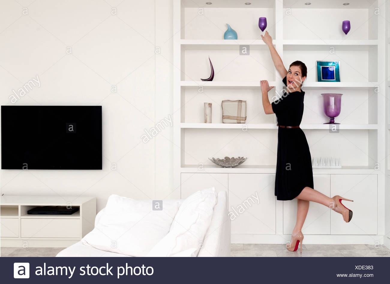 Young woman reaching for wine glass on shelf in living room - Stock Image