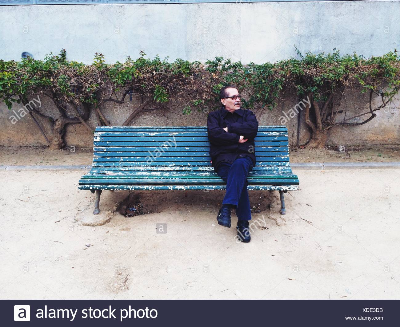 Full Length Of Mature Man Looking Away While Relaxing On Park Bench - Stock Image
