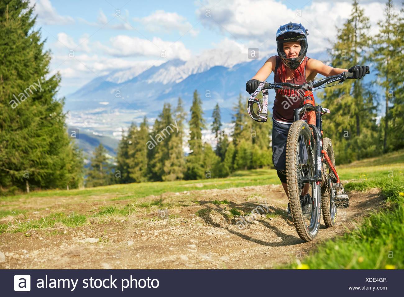 Downhill biker pushing mountain bike downhill on a trail, Inn Valley behind, Mutterer Alm, Muttereralmpark, Mutters, Tyrol - Stock Image