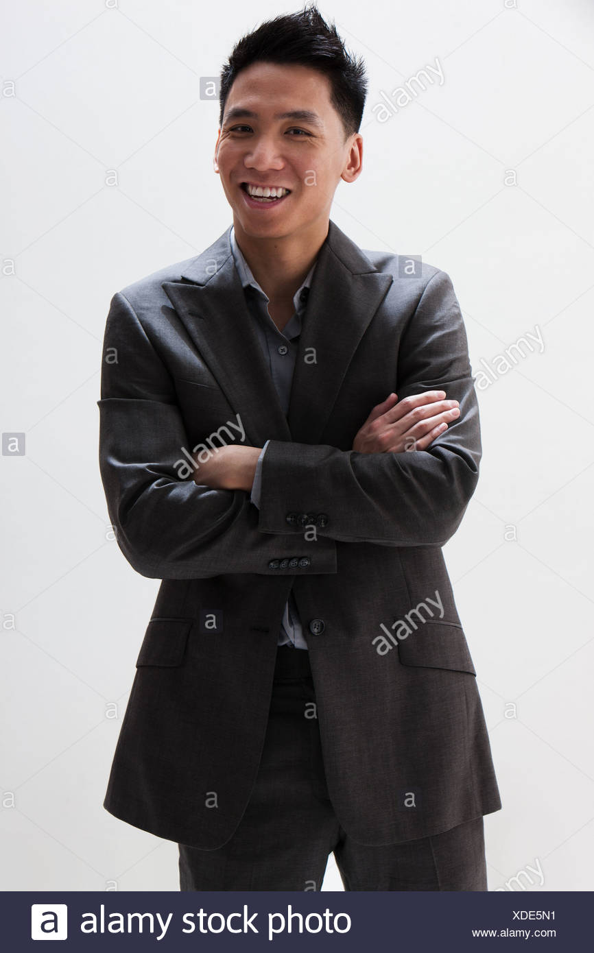Young Asian businessman smiling, studio shot - Stock Image