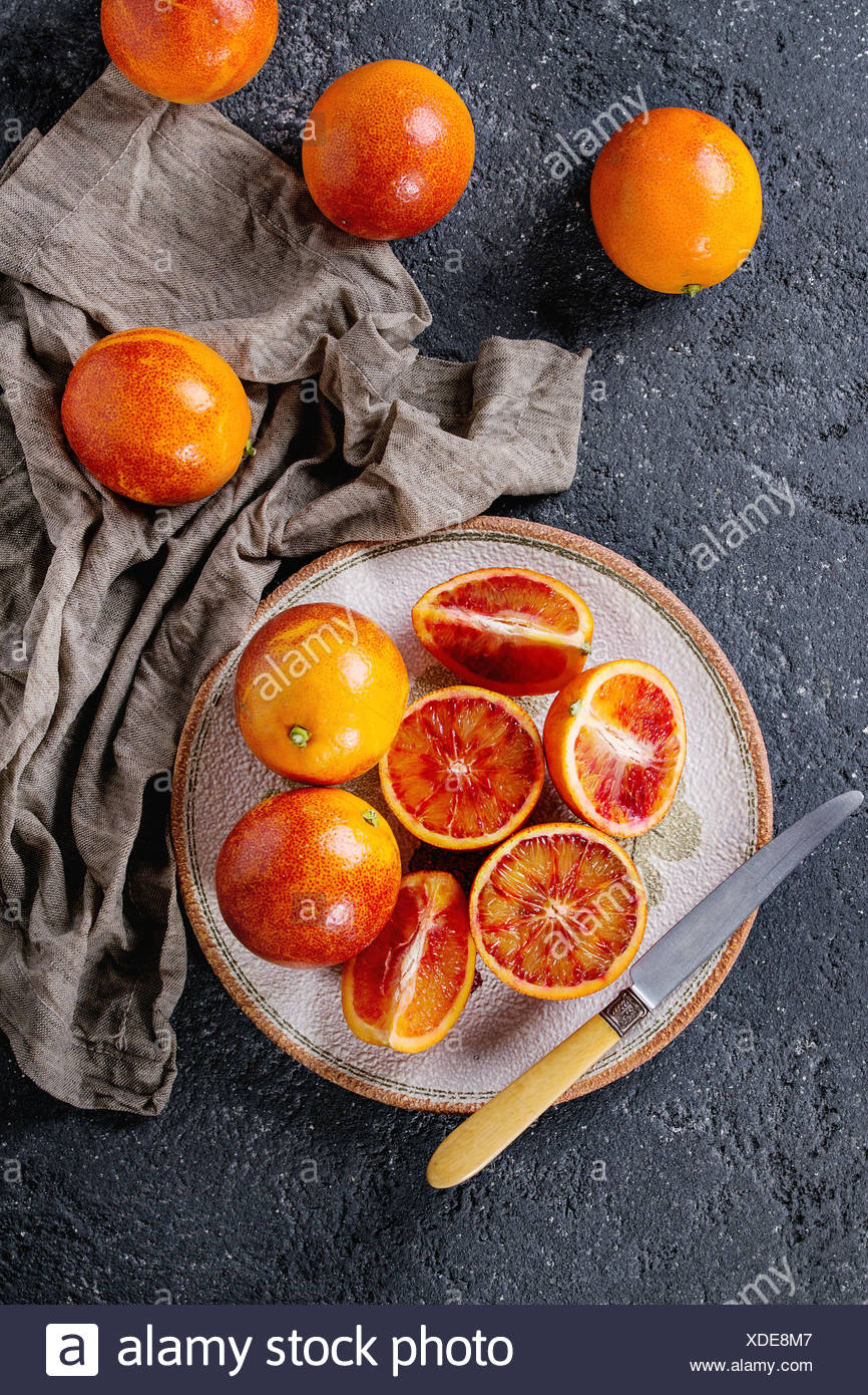 Sliced and whole ripe juicy Sicilian Blood oranges fruits with knife, sackcloth rag on ceramic plate over black concrete texture background. Top view - Stock Image