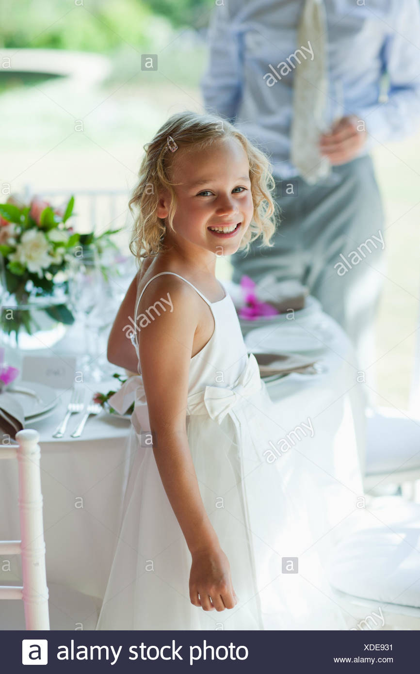 Smiling girl standing at wedding reception - Stock Image