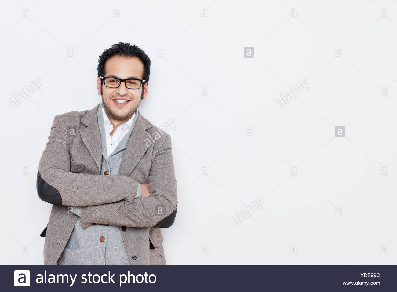 Businessman standing with arms folded - Stock Image