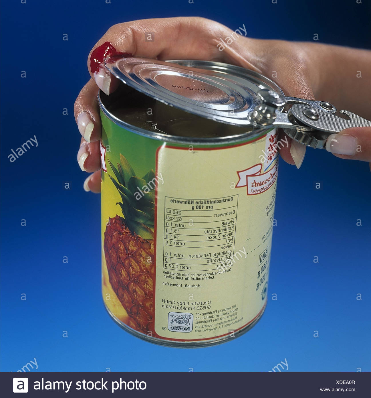 Woman, detail, hands, canned food tin, open, injury, studio, women's hands, tin, canned food, pineapple, fruit, long-lasting, durability, tin, tin, injury danger, danger, dangerously, editing, cut, can opener - Stock Image