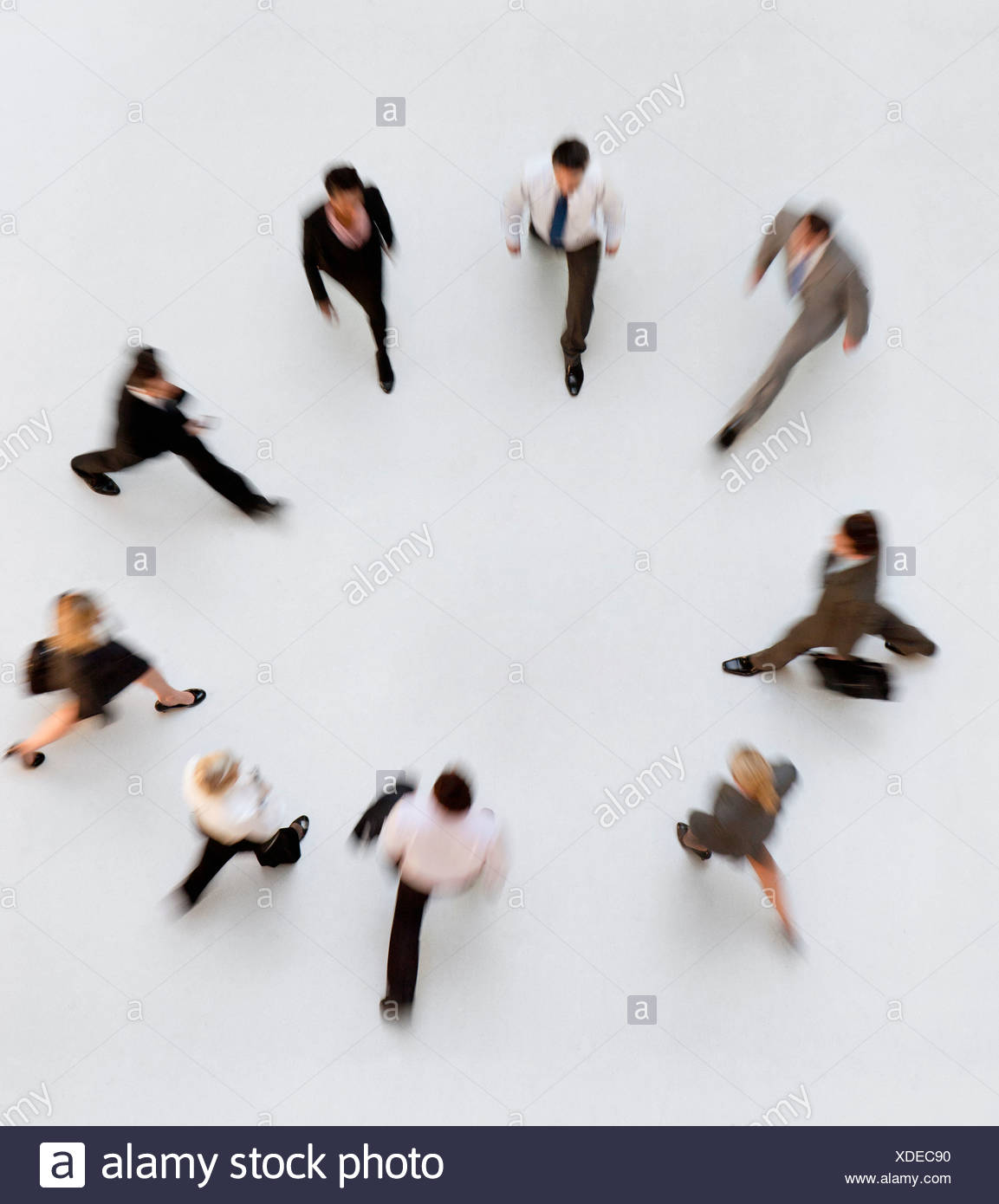Walking business people forming a circle - Stock Image