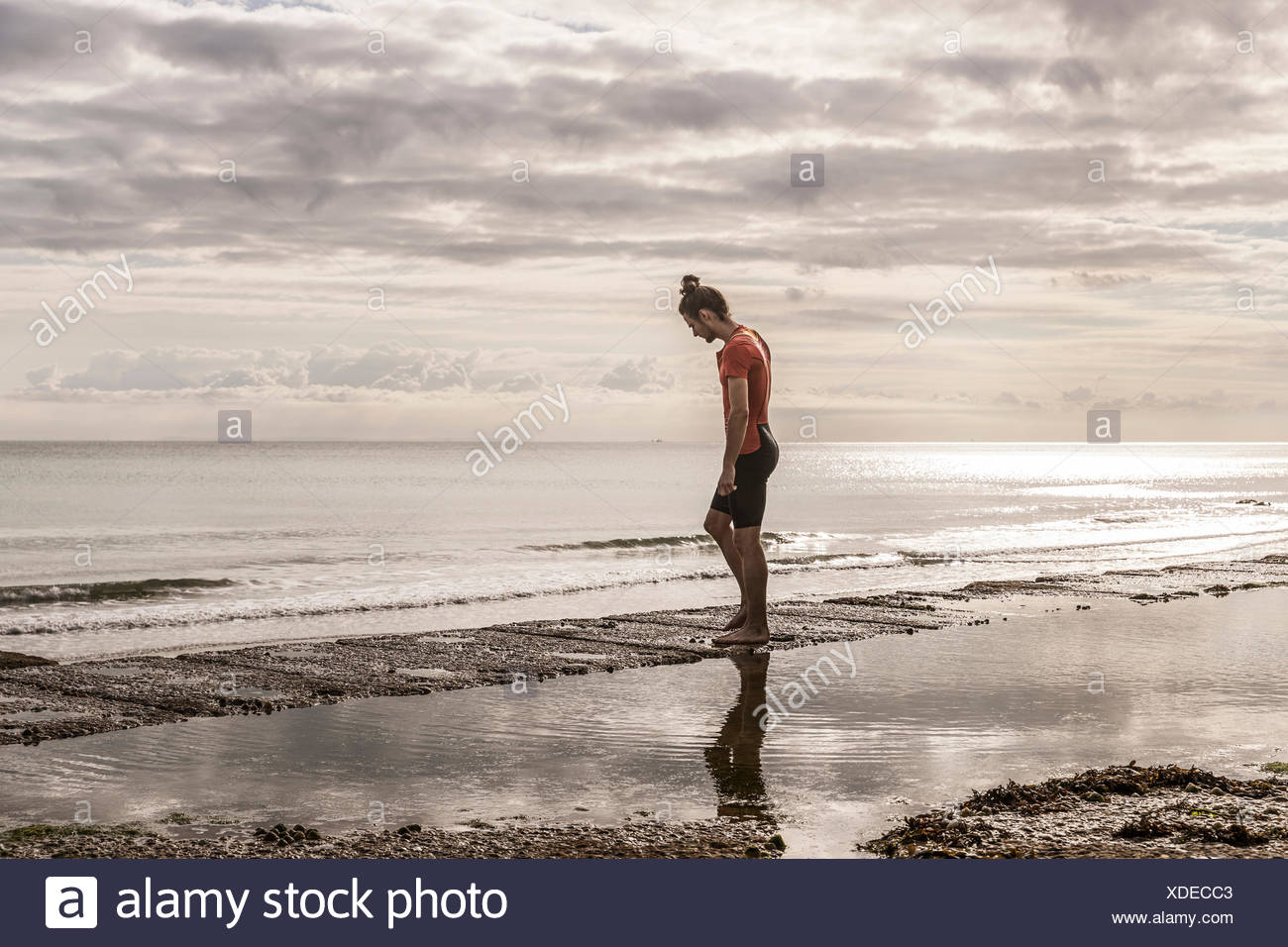 Man on shoreline looking away at view of sea - Stock Image