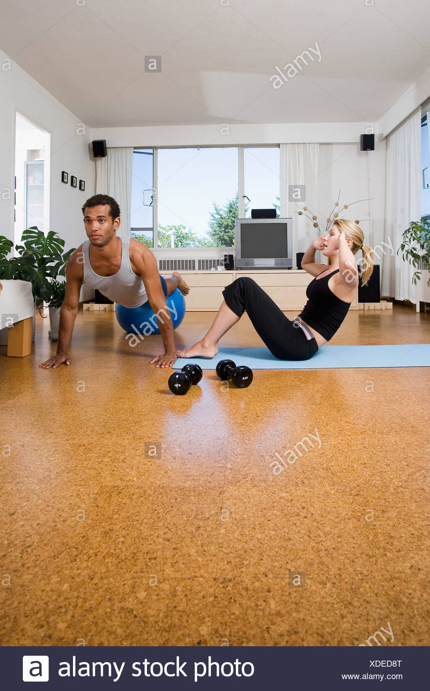 Young couple exercise at home, performing sit-ups and push-ups, Vancouver, British Columbia - Stock Image